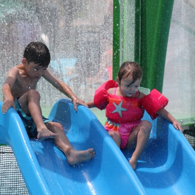 Two children go down the water feature's slide together.