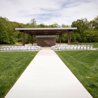 White chairs are set up for an outdoor wedding at the Amphitheater