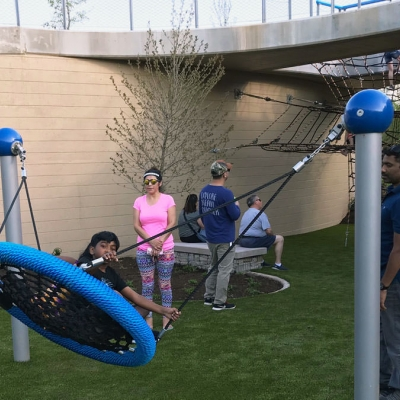 Parents push children on a saucer-style swing
