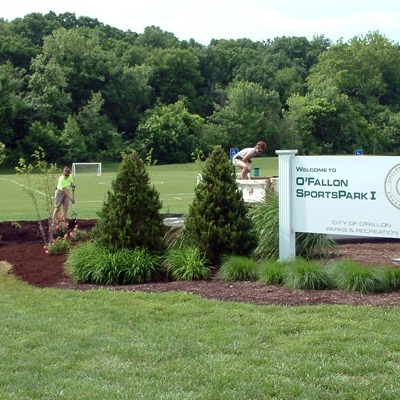 Landscaping workers mulch new plantings at the entrance to Sports Park